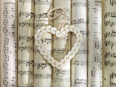 Scrolls of sheet music with heart made of buttons