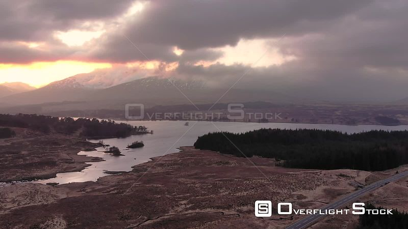 Aerial drone shot of sunset behind mountains in Glencoe, Highlands of Scotland
