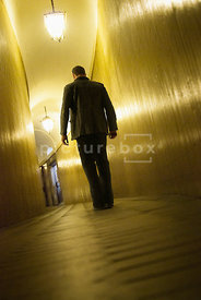 An atmospheric image of a lone mystery man, in a leather jacket, walking down the dimly lit corridor of an old building.