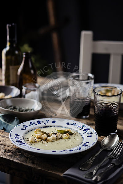Cauliflower cream soup on a wooden dining table.