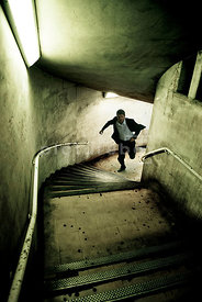 An atmospheric image of a mystery man running up some dirty, old characterful steps from the underground, London, England.