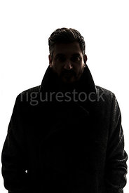 A silhouette of a mystery man in a big coat, looking at camera – shot from eye level.