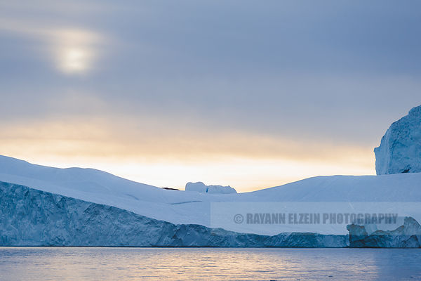 Very large iceberg in Ilulissat, with the sun rising above it