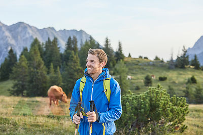 Austria, Tyrol, Mieming Plateau, portrait of smiling hiker on alpine meadow