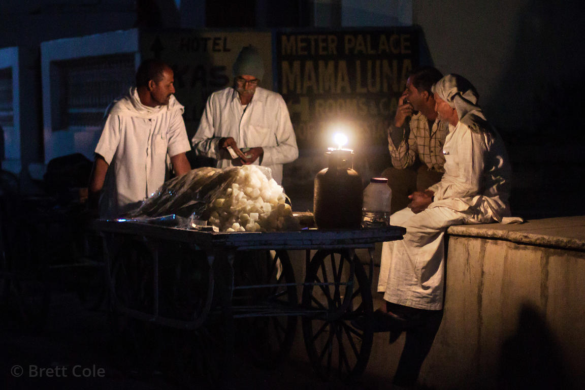 Men drink chai tea before sunrise on a street in Pushkar, India.