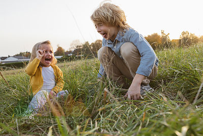 Brother and his little sister screaming on a meadow