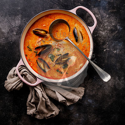 Seafood soup with prawns, mussels and tomato on dark background