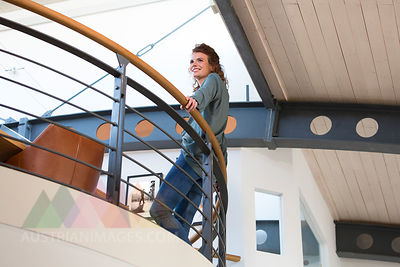 Smiling woman leaning against railing in modern office