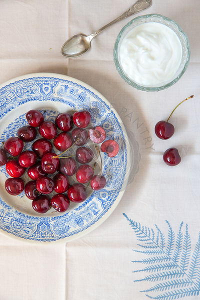 whole cherries on blue ceramic plate, on leaf linen and cream or yogurt in glass dish with vintage spoon
