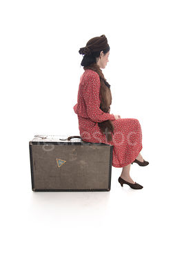 A 1940's woman in a hat and fur, sitting on a suitcase – shot from mid-level.
