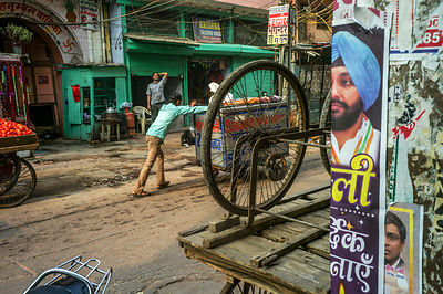 A Vendor Pushes His Cart Past A Political Poster