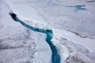 Aerial view of ice cap north-east of Sermeq Kujalleq Glacier with meltwater channel disappearing in a moulin, Sermersuaq / Gr...