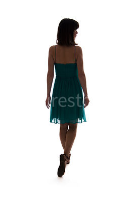 A semi-silhouette of a woman in a dress walking away – shot from eye level.
