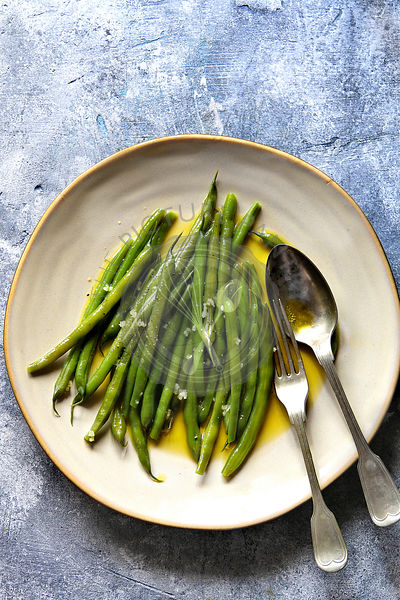Sauteed green beans with olive oil and garlic on a serving plateTop view