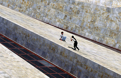 Children play on the sides of a Socialist monument in Tirana, Albania