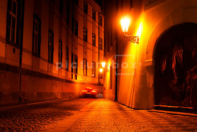 Car speeding down a Prague street at night.