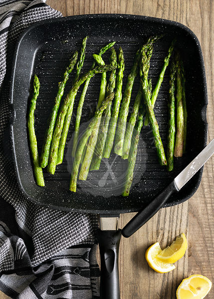 Asparagus spears cooking in a chargrill pan.