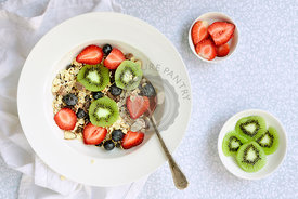 Bowl of muesli, sliced kiwi fruit, strawberries and blueberries with a spoon for breakfast.