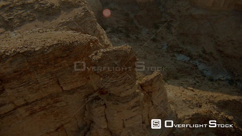Aerial close up sides of rocky outcrop and around single weathered pillar of rock with desert terrain below Fish River Canyon...