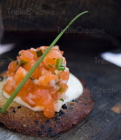 Salmon tartar on sesame crisps with creme fraiche served on wooden platter
