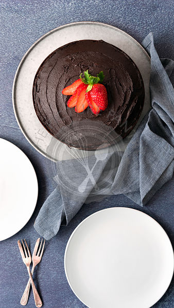Round gluten-free chocolate cake with two plates and two cake forks.