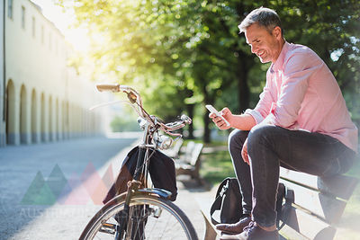 Smiling man with bicycle checking the phone on a park bench