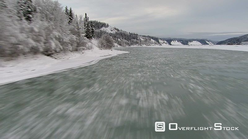 Fast, low flight along icy river's course in Alaska