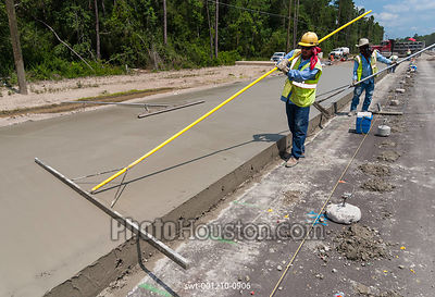 Highway construction workers smoothing freshly poured concrete