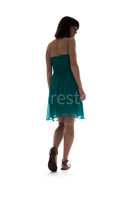 A semi-silhouette of a woman in a dress walking away – shot from low level.