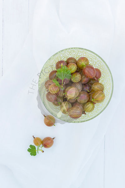 Fresh fruit gooseberries in a green bowl.
