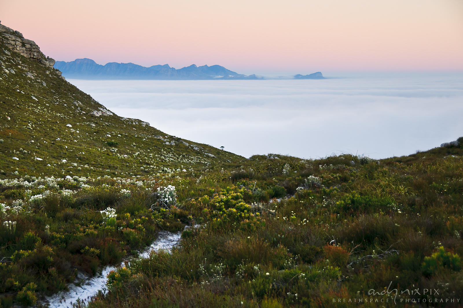 Fog over False Bay viewed from Muizenberg Peak (Farmer Peck's Valley), distant mountains visable above cloud