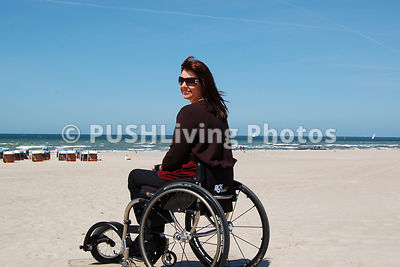 Young woman using a wheelchair at the beach