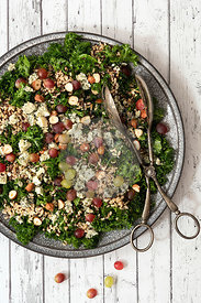 Kale, mixed grain, hazelnut and grape salad with serving tongs.