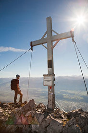 Alpinist stands on mountain top, looking at view, Innsbruck route, Tyrol, Austria