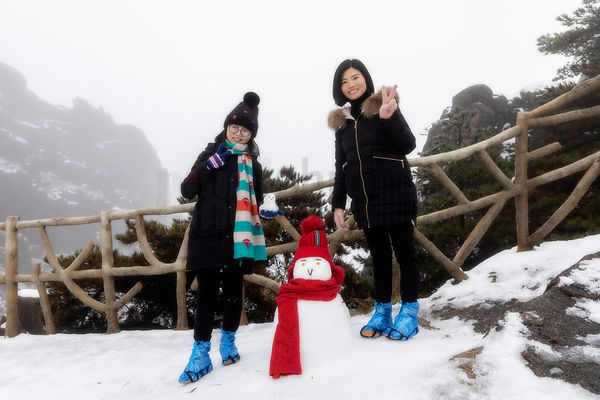Chinese Tourists and Snowman in the Huangshan Mountains