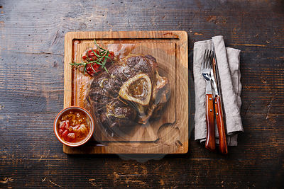 Prepared Osso buco Veal shank with tomatoes on serving board on wooden background