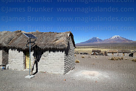 Solar panel next to thatched adobe house in Estancia Huincurata, Payachatas volcanos in background, Sajama National Park, Bol...