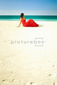 An atmospheric image of a woman in a red dress sitting on a tropical beach.