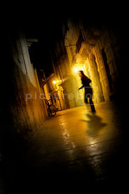 An atmospheric image of of a woman being chased down an empty street lit by streetlights at night.