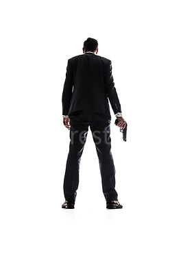 A mystery man in a suit, standing with a gun and looking away, in silhouette – shot from low level.