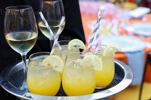 White wine and lemonade glasses being served on a tray