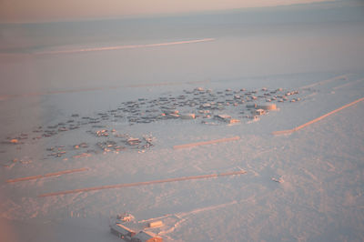 Aerial view of the snow-covered coastal Arctic village of Kaktovik in autumn, Barter Island, and the Beaufort Sea in the dist...