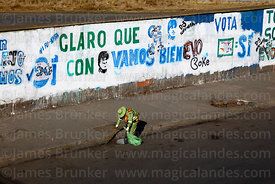 Street cleaner working in front of  slogans on wall showing support for Evo Morales, El Alto, Bolivia