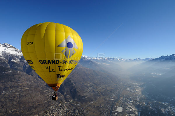 Hot air balloon in flight over the Aosta Valley, northern Italian Alps, with early morning mist / temperature inversion