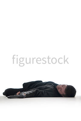 A Figurestock image of a man with a gun, laying dead on the floor – shot from low level.