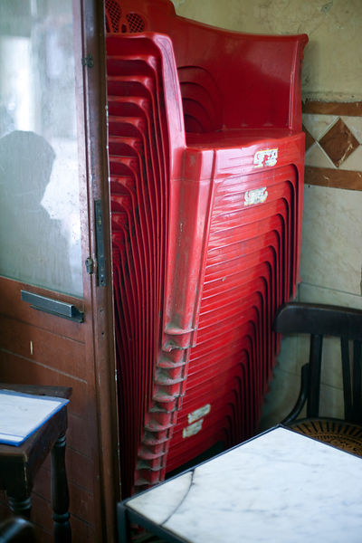 Egypt - Cairo - Details of stacked red chairs and damp on the wall at the Telegraph Cafe, off Halim Square, Cairo