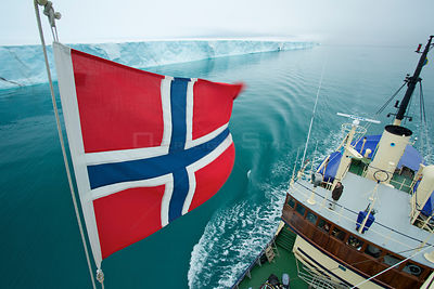 Norwegian flag set on M/S Stockholm and ice front of Brasvellbreen seen from crow's nest, Austfonna, Nordaustlandet, Svalbard...