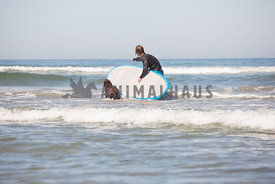 man in the ocean with his dog and surfboard