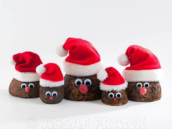 Christmas puddings with Santa hat on white background