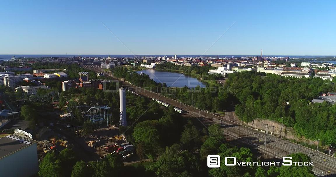 Train in a City, Aerial Tracking View Following a Train Leaving the Railway Station, in Helsinki, on a Sunny Summer Morning D...